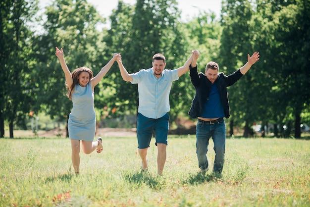Amici soddisfatti che corrono e che tengono le mani in alto