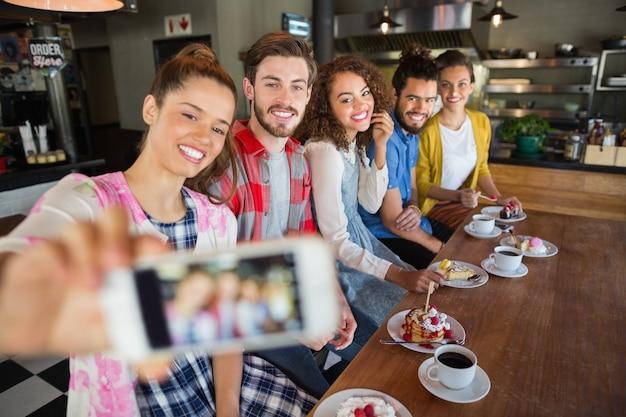 Amici sorridenti che catturano foto nel pub