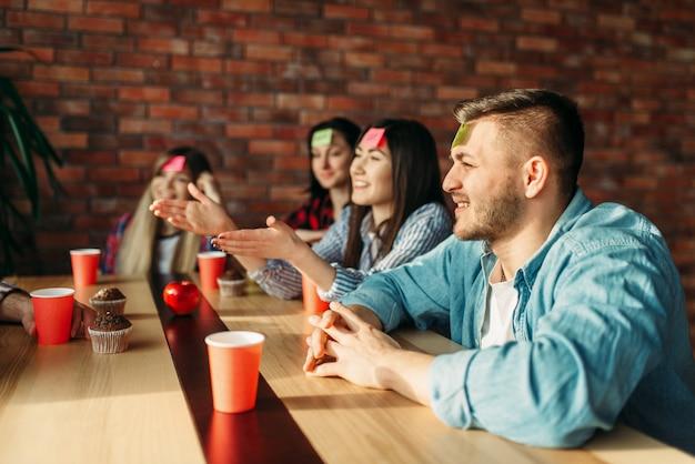 Amici sorridenti che giocano le note dell'autoadesivo alla fronte