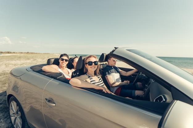 Amici sorridenti che guidano auto vicino al mare e divertirsi