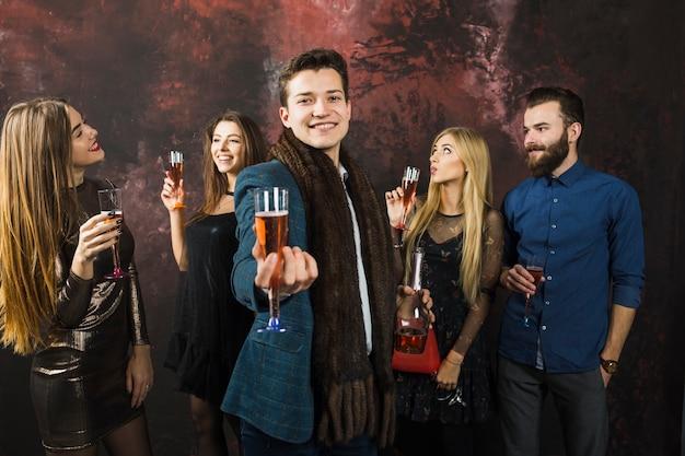 Amici sorridenti che mostrano i vetri del champagne