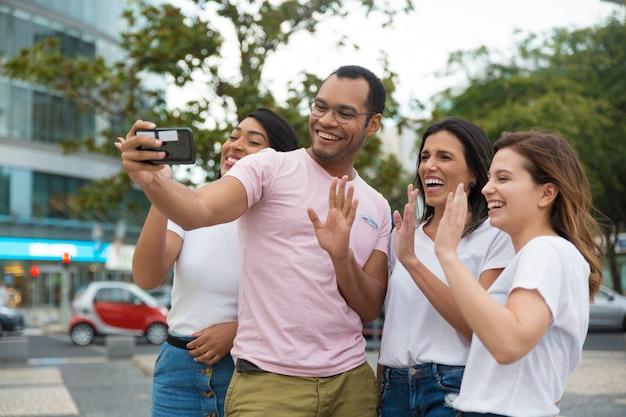 Amici sorridenti che ondeggiano al telefono della macchina fotografica