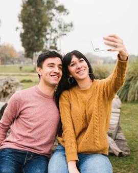 Amici sorridenti che prendono selfie nel parco
