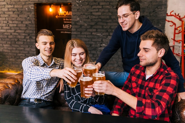 Amici sorridenti che si siedono insieme tostando i vetri di birra