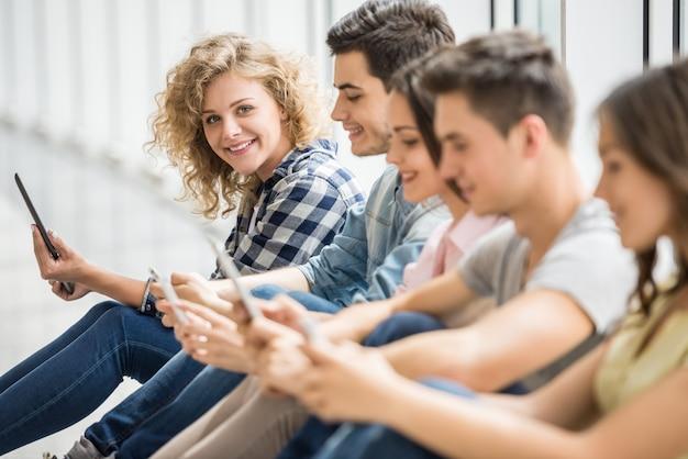 Amici sorridenti che si siedono sul pavimento e che guardano le foto.