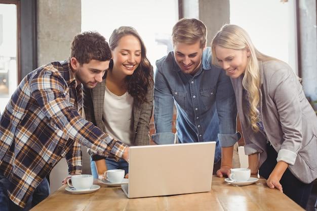 Amici sorridenti che stanno e che indicano sullo schermo del computer portatile