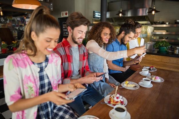 Amici sorridenti che utilizzano i loro telefoni cellulari nel ristorante