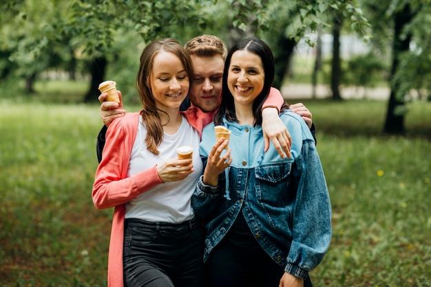 Amici sorridenti che vanno in giro nel parco con il gelato