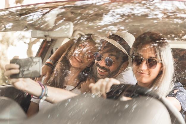 Amici sorridenti che viaggiano in auto prendendo selfie attraverso il cellulare