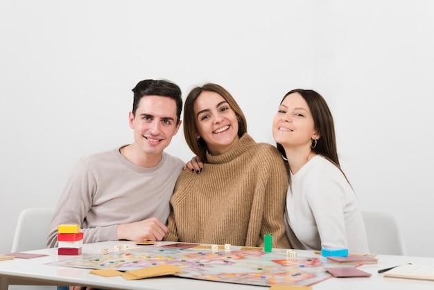 Amici sorridenti di vista frontale che giocano un gioco da tavolo
