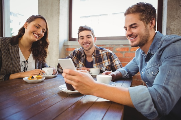 Amici sorridenti guardando smartphone