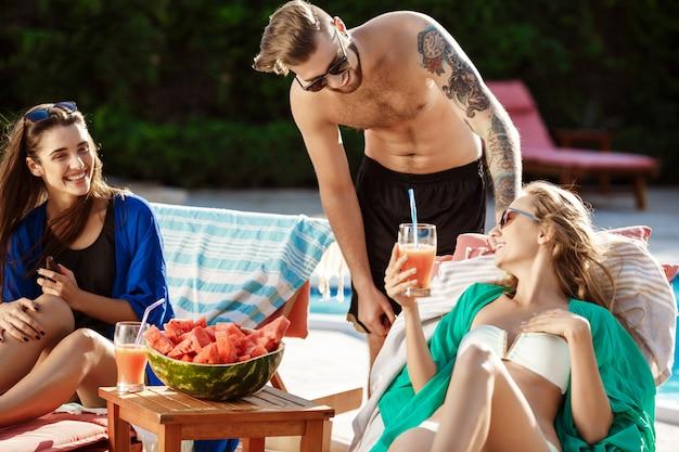 Amici sorridenti, mangiando anguria, bevendo cocktail, rilassandosi vicino alla piscina