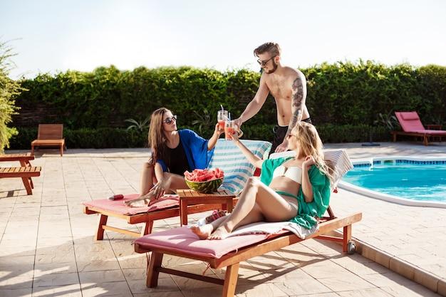 Amici sorridenti, prendere il sole, bere cocktail, sdraiato vicino alla piscina