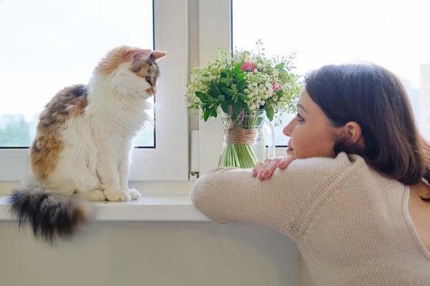 Amicizia della donna matura e del gatto tricolore adulto