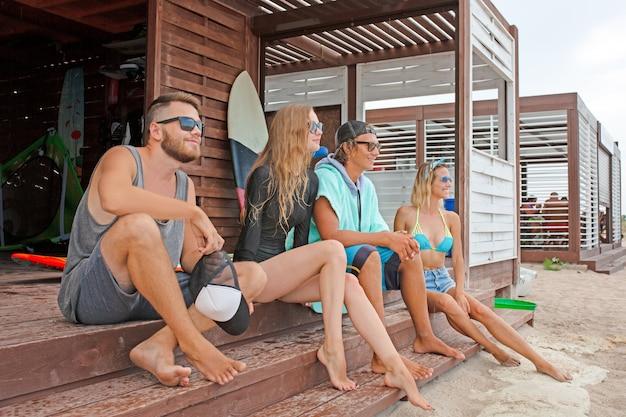 Amicizia, mare, vacanze estive, sport acquatici e concetto della gente - gruppo di amici che indossano costumi da bagno che si siedono con i surf sulla spiaggia