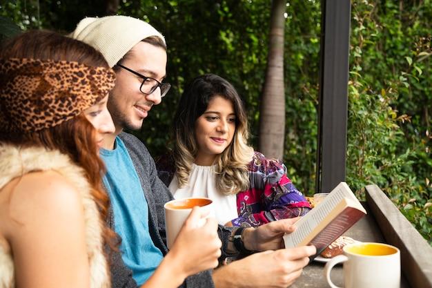 Amico che legge un libro alla caffetteria