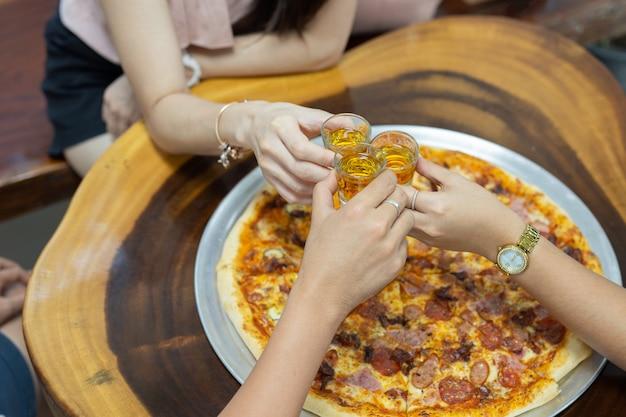 Amico con rum colpi sulla festa con pizza sul tavolo.