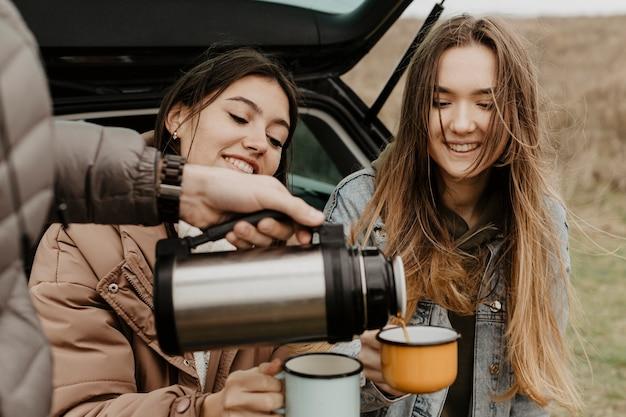 Amico dell'angolo alto che versa tè per gli altri