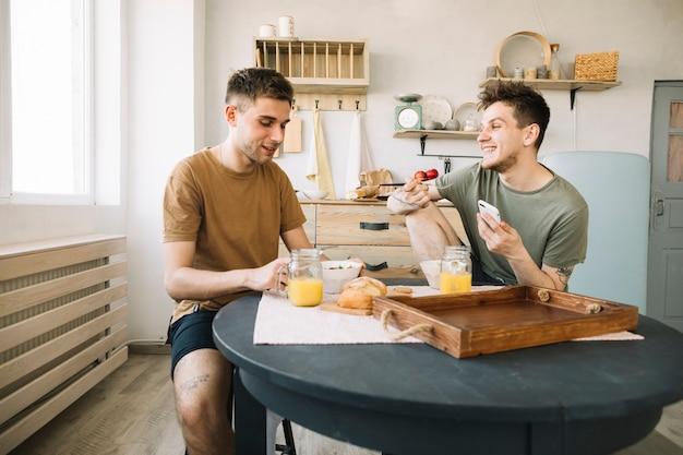 Amico sorridente che gode del cibo delizioso sul tavolo dinning in cucina