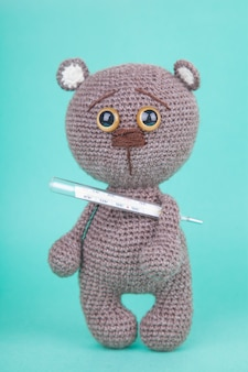 Amigurumi. giocattolo fai da te. cucciolo di orso bruno a maglia con termometro. , prevenzione delle malattie infantili