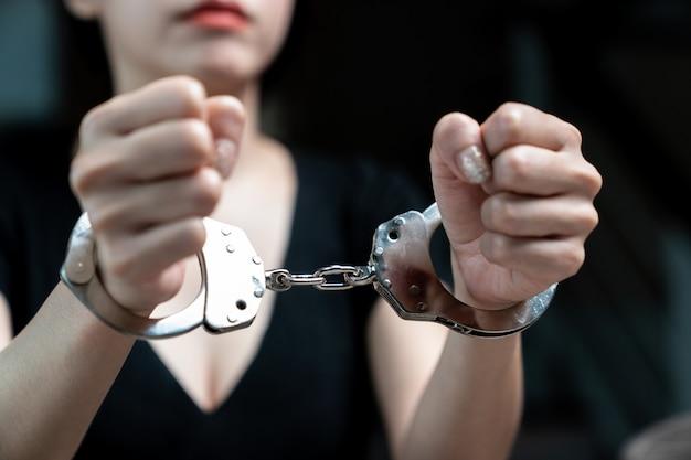 Ammanettato a un prigioniero, le donne prigioniere erano ammanettate nella prigione buia.