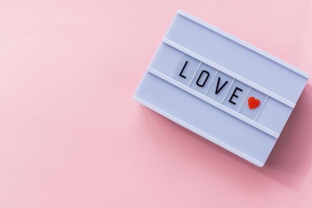 Amo il testo in una scatola luminosa. scatola isolata sopra fondo rosa. un segno con un messaggio. bandiera di san valentino. sfondo di vacanza, carta festiva. copia spazio. può essere utilizzato per celebrazioni san valentino.