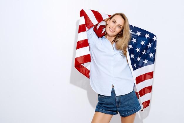 Amo l'america. ragazza che tiene una bandiera americana su fondo e sul sorriso bianchi. il concetto di migrazione e delle festività nazionali e il giorno dell'indipendenza dell'indipendenza d'america il 4 luglio
