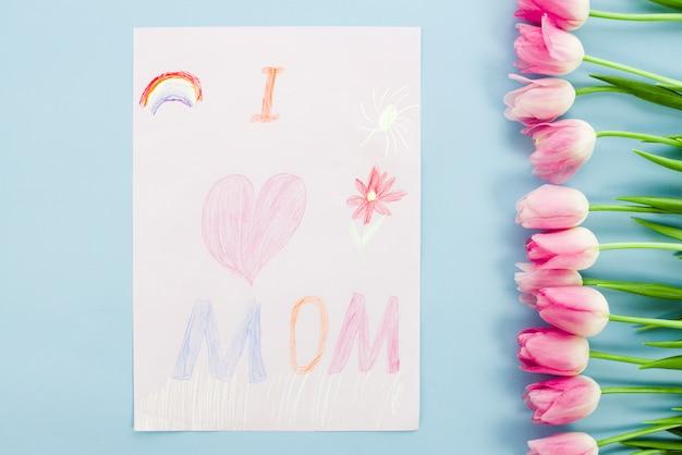 Amo la mamma che disegna su carta con i tulipani