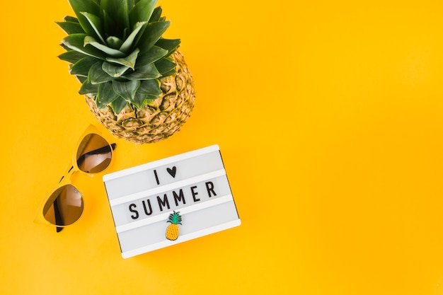 Amo la scatola luminosa estiva; occhiali da sole e ananas su sfondo giallo