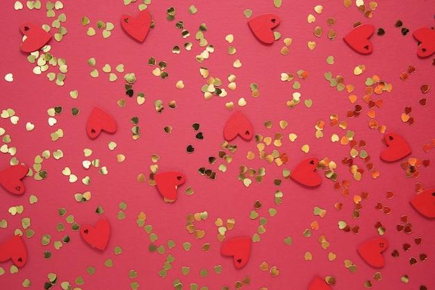 Amore astratto sfondo rosso con glitter a forma di cuore d'oro. san valentino piatto disteso.