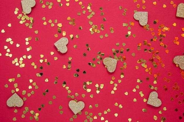 Amore astratto sfondo rosso con glitter dorati. piatto o festa di san valentino disteso.