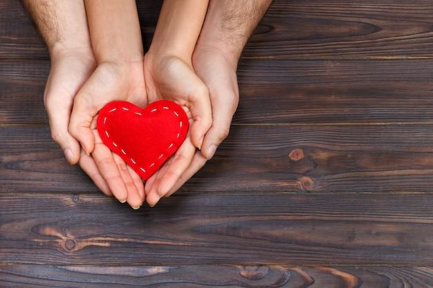 Amore, concetto di famiglia. chiuda su delle mani della donna e dell'uomo che tengono insieme il cuore di gomma rosso