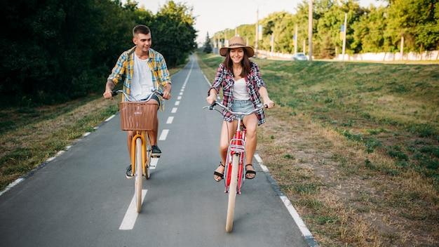 Amore coppia cavalcando biciclette retrò nel parco estivo