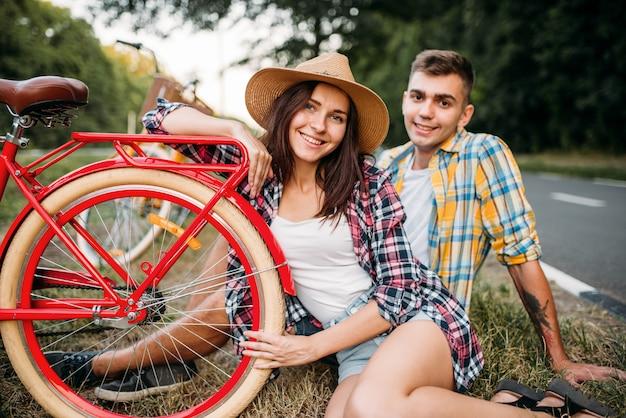 Amore coppia con bici vintage seduto sul ciglio della strada. viaggio romantico di giovane uomo e donna. ragazzo e ragazza insieme all'aperto, bicicletta retrò