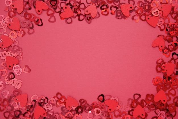 Amore cornice astratta, bordo, sfondo rosso con glitter a forma di cuore. san valentino piatto disteso.