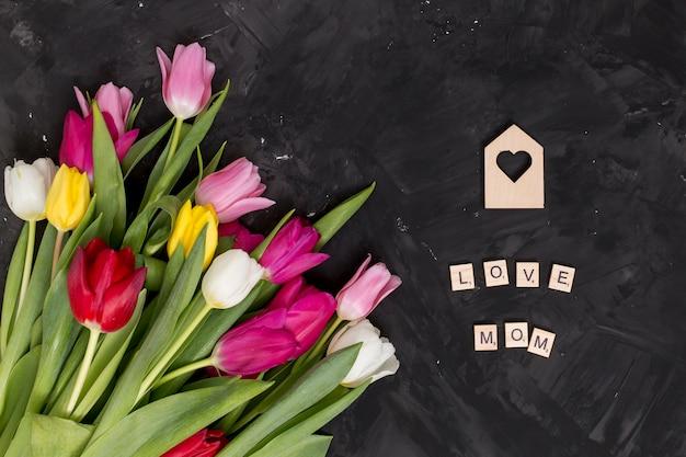 Amore; mamma; l'alfabeto sui blocchi di legno con forma del cuore e fiori variopinti del tulipano sopra il contesto nero