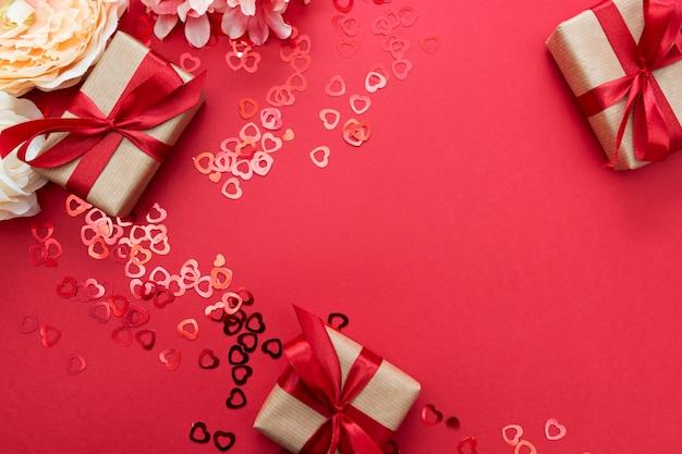 Amore, modello di cornice di san valentino. contenitore di regalo avvolto con la carta kraft e l'arco rosso isolati su fondo rosso.