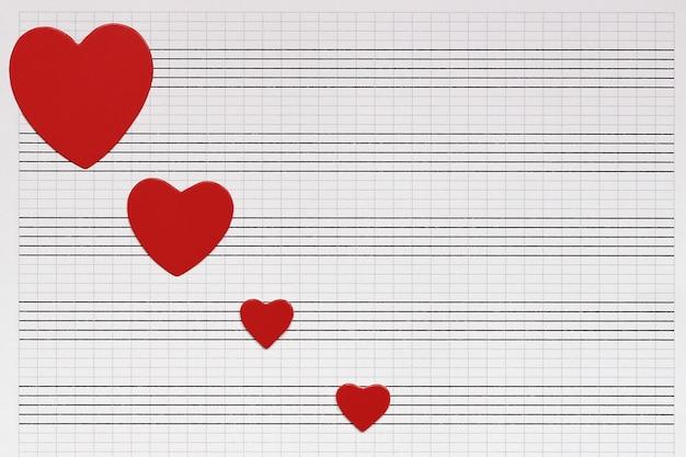 Amore, musica e cuori cuori di carta rossa giacciono su un taccuino musicale pulito.