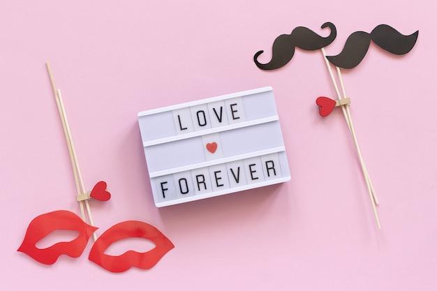 Amore per sempre testo di casella di luce, paio di baffi di carta, puntelli di labbra sul rosa