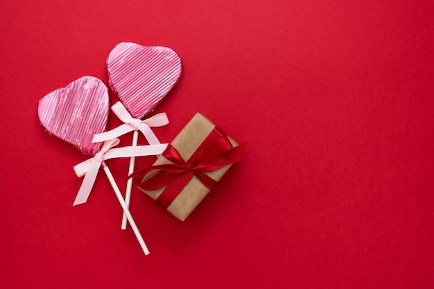 Amore, san valentino mock up, con lecca-lecca a forma di cuore e regalo boxex, isolato su sfondo rosso, copia spazio.