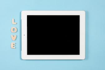 Amore testo in legno vicino alla tavoletta digitale con display nero su sfondo blu