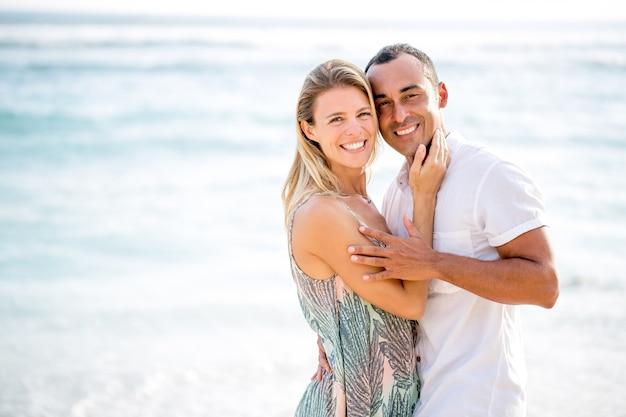 Amorevole coppia che abbraccia sulla spiaggia di mare di estate