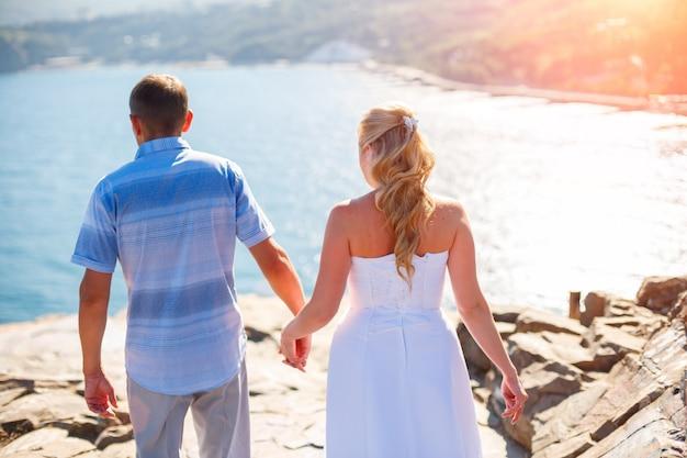 Amorevole coppia tenendo le mani va alla scogliera dal concetto di turismo del mare