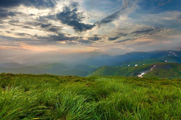 Ampia vista sulle montagne d'estate all'alba. sole arancione d'ardore che si alza in cielo nuvoloso blu sopra l'erba molle della collina erbosa verde e la catena montuosa distante coperte di foschia di mattina. bellezza del concetto di natura.