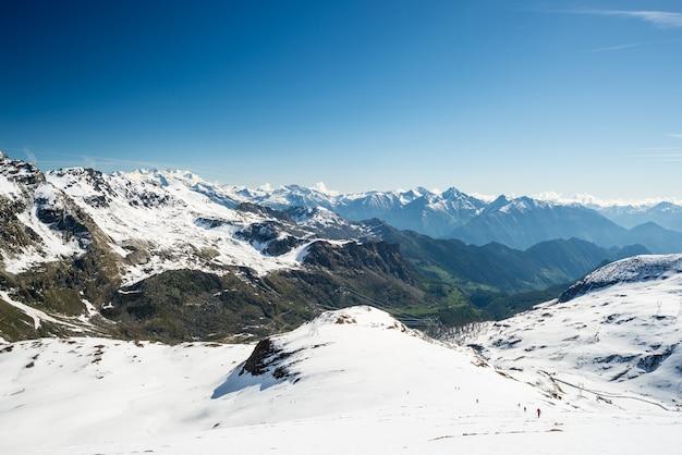 Ampio angolo di visione di una stazione sciistica in lontananza con eleganti picchi montuosi