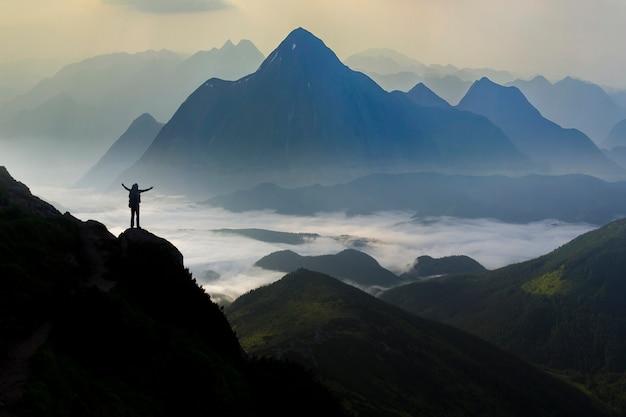 Ampio panorama montano. piccola sagoma di turista con zaino sulla montagna rocciosa.