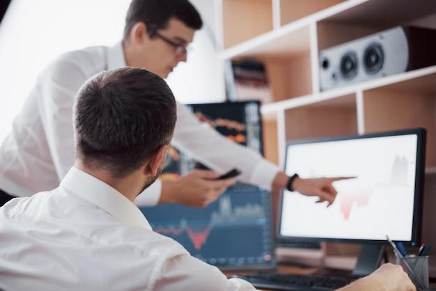 Analisi dei dati primo piano di giovane squadra di affari che lavora insieme in ufficio creativo mentre giovane donna che punta sui dati presentati nel grafico con la penna