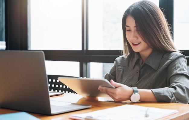 Analizzi il computer della compressa di uso della giovane donna per l'affare