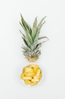 Ananas affettato in una ciotola bianca sulla vista bianca e superiore.