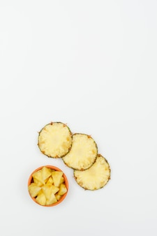 Ananas affettato in una ciotola dell'argilla su un bianco. vista dall'alto.